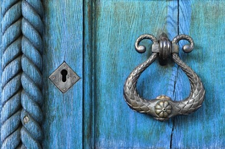 image of weathered door and ornate door knocker and key hole, suggesting home organizer value of possibility and transformation