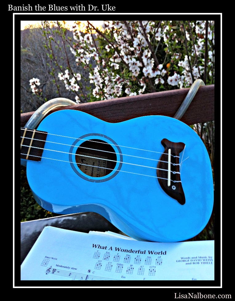 Banish the Blue with Dr. Uke by Lisa Nalbone blue dolphin ukulele in sunset on deck with almond blossoms and What a Wonderful World music.