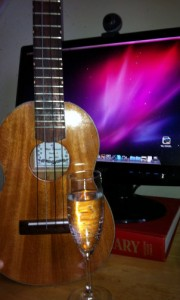 Ukulele and glass of champagne in front of computer.