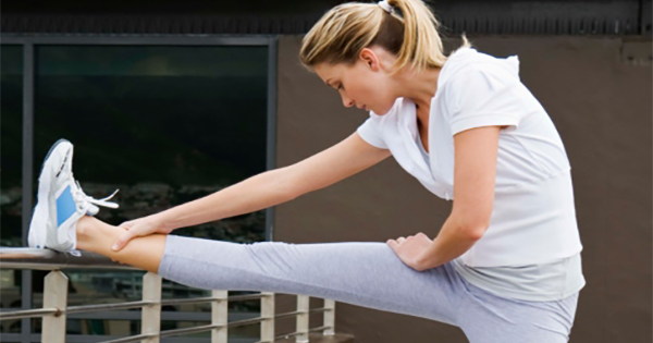 Woman stretching with raised leg over railing