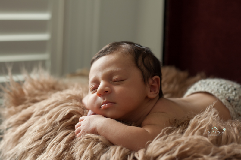 picture of newborn with head on hands