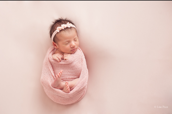 Precious baby photo of sleeping baby girl swaddled in pink wrap with pretty headband