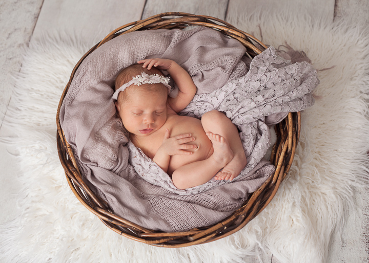 newborn girl in basket wrapped in mauve