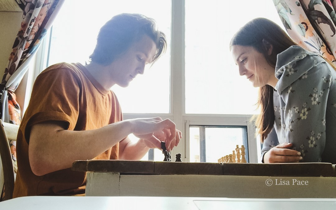 couple sitting by window playing chess