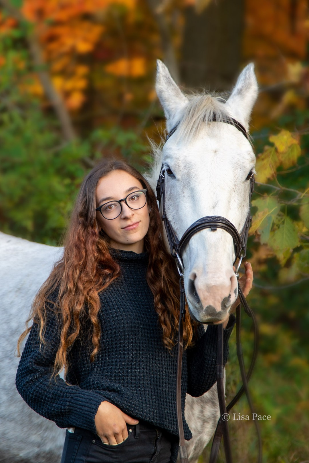 young woman posing with grey horse fall colours
