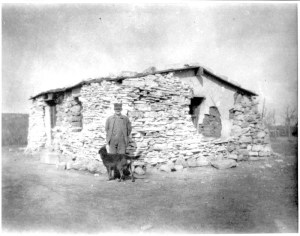 Man standing with dog outside of a sod house, C. 1913 (Library of Congress)