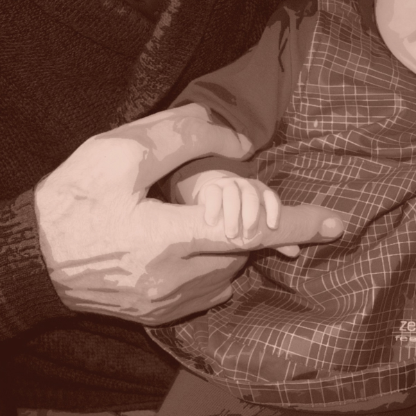 A closeup of a baby grasping the hand of the older person holding him. (Photo © FreeImages/Iwan Boin)