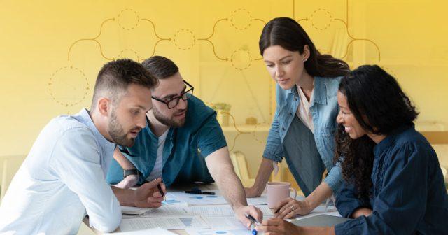 quatre personnes examinant des documents commerciaux sur une table pour réaliser un processus de marketing par e-mail agile