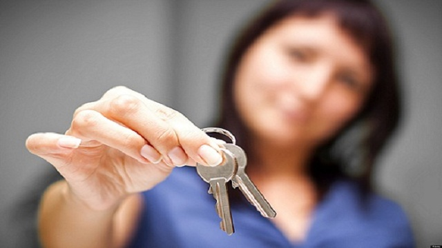 Realtor is giving the keys to an apartment to some clients. focus on the keys