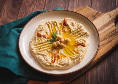 Plato de hummus en una tabla de cortar: ¿pueden los gatos comer hummus?