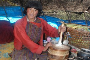 A Bjob woman churns butter inside her Bja (tent) in the higher mountains of Bhutan.