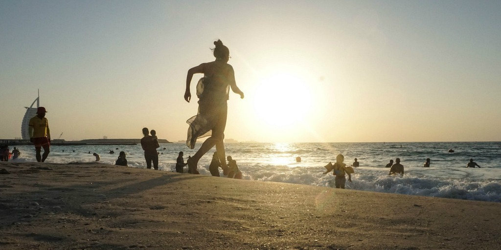 What should you wear on the beach in Dubai - girl running along Jumeirah sunset beach