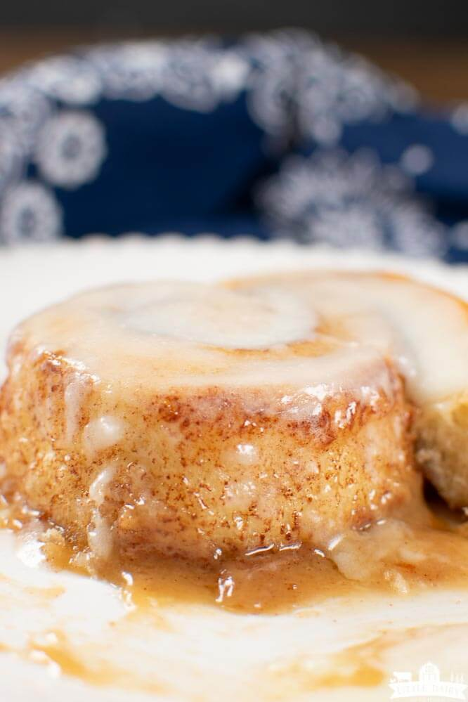 an unrolled cinnamon roll nestled in golden brown caramel sauce and frosted with cream cheese icing.