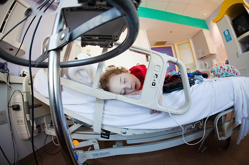 Toddler sleeping in hospital bed at Texas Children's Hospital.