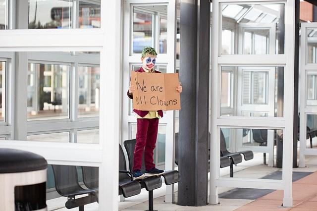 Boy in bus station dressed as joker.