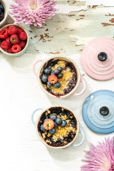 A raspberry and blueberry crisp recipe on a white table with pink and blue Le Creuset lids.