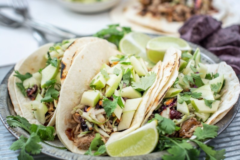 Carnitas BBQ pulled pork tacos with apple salsa and a lime slice