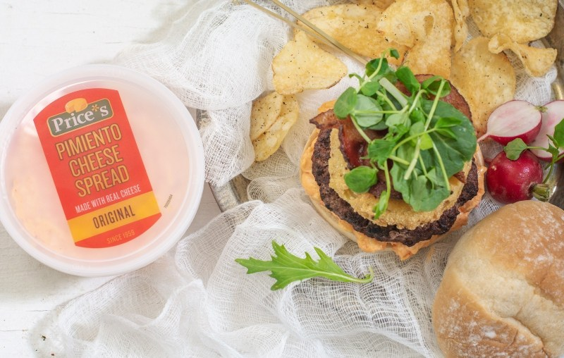 Prices pimiento cheese in packaging beside a hamburger with toppings