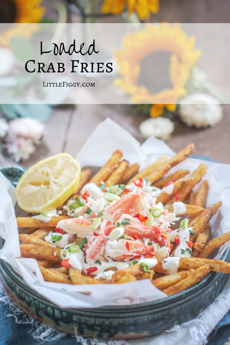 Loaded Crab Fries with sunflowers on brown table