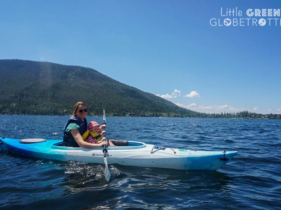Mother and son kayak together on Grand Lake, Colorado. The boy is wearing a Frugi sun hat.