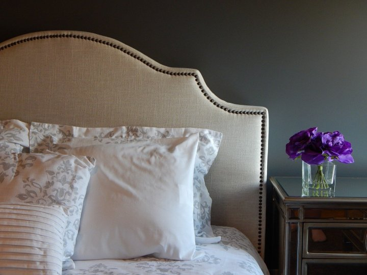 A bed with a fabric covered headboard. A nightstand to the right, with a small vase of flowers.