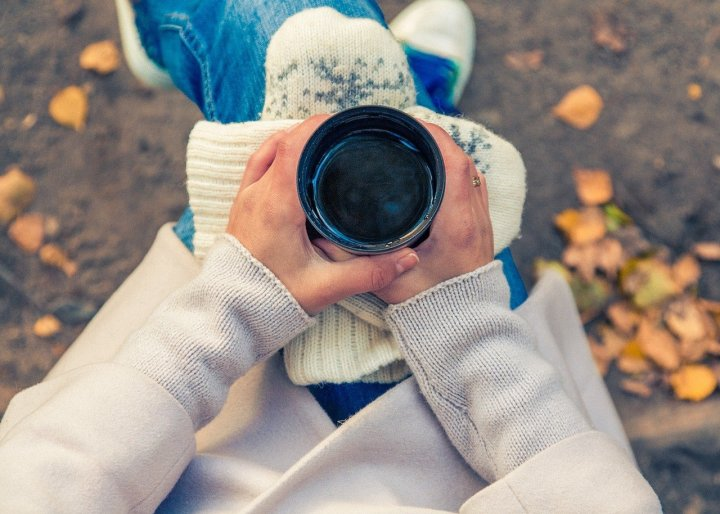 A woman is holding a coffee cup, wearing a sweater and jeans. Fallen leaves are in the background.