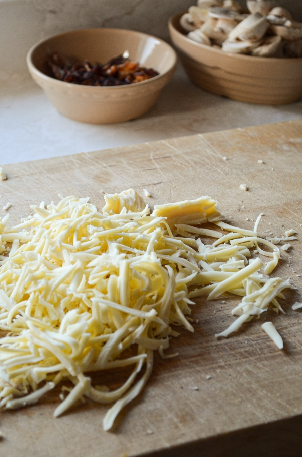 Shredded mozzarella cheese is resting on a wood cutting board, with mushrooms and bacon in the background.