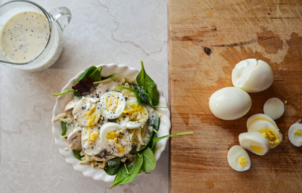 A delicious bowl of baby spinach salad, with hard boiled eggs on the side, resting on a wood cutting board.