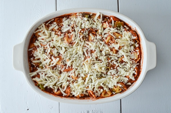 A baking dish is filled with tortellini and pasta sauce. Topped with shredded mozzarella cheese.