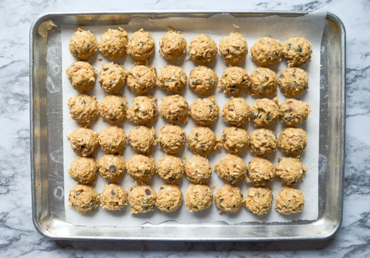 A baking sheet full of portioned buffalo chip cookie dough.