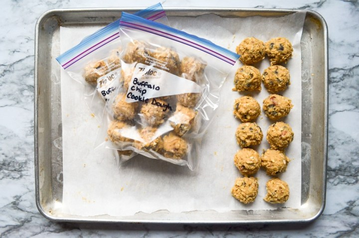 A baking sheet with cooking dough portioned to the right, and freezer bags with frozen dough in the center of the sheet.