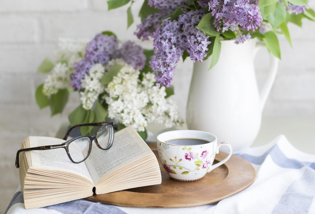 Book nook, book with glasses, cup and a picture of lilacs.