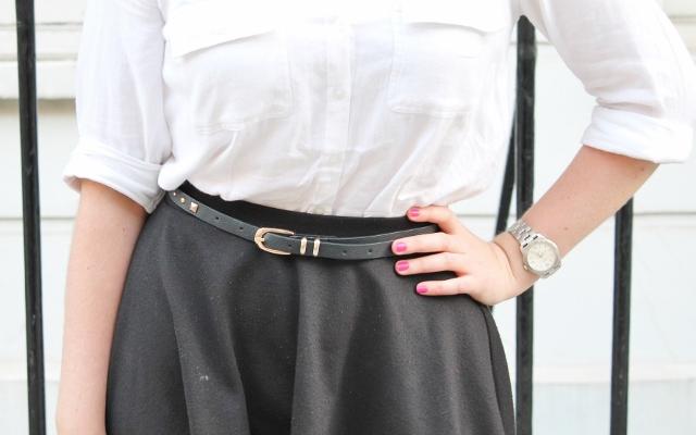 White shirt, black skirt, gold buckle belt, pink nails, silver watch