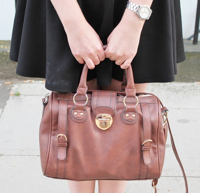 Tan bag, black skirt, silver watch