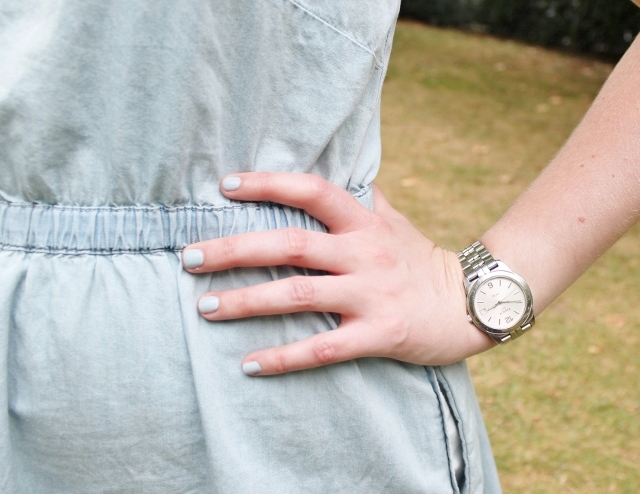Hand on hip, pale blue nail polish, silver watch.