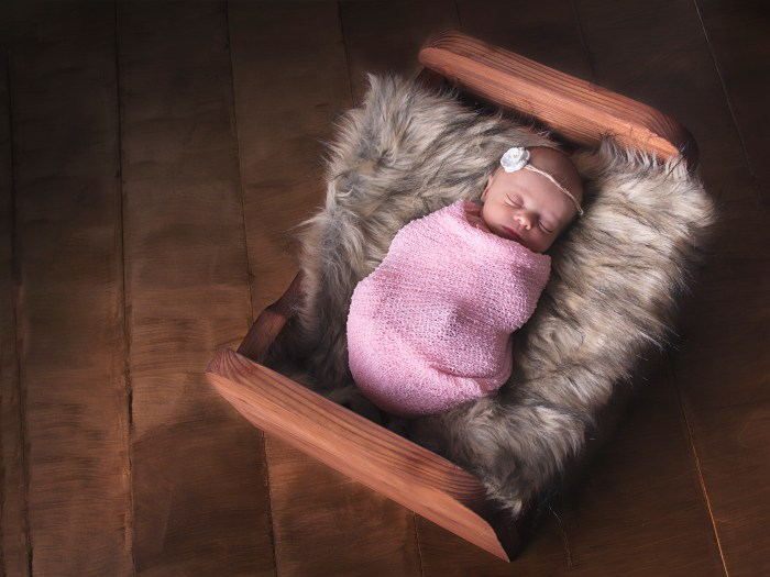 tiny baby in wooden bed