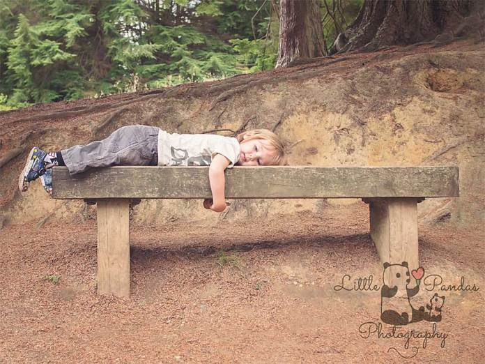 Little boy laying on bench