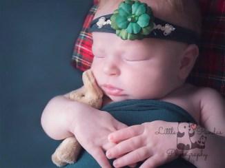 Baby girl cuddling rabbit green background