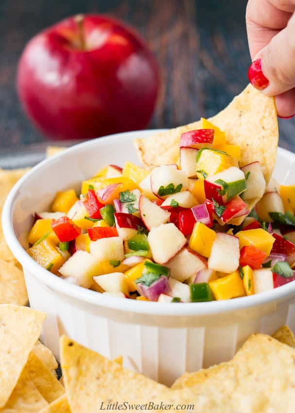 Apple mango salsa in a white bowl surrounded by tortilla chips with a hand dipping a chip.