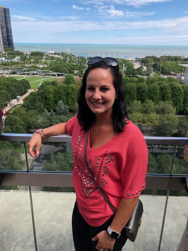Woman in pink short sleeve blouse standing on rooftop terrace with Chicago lakefront in background