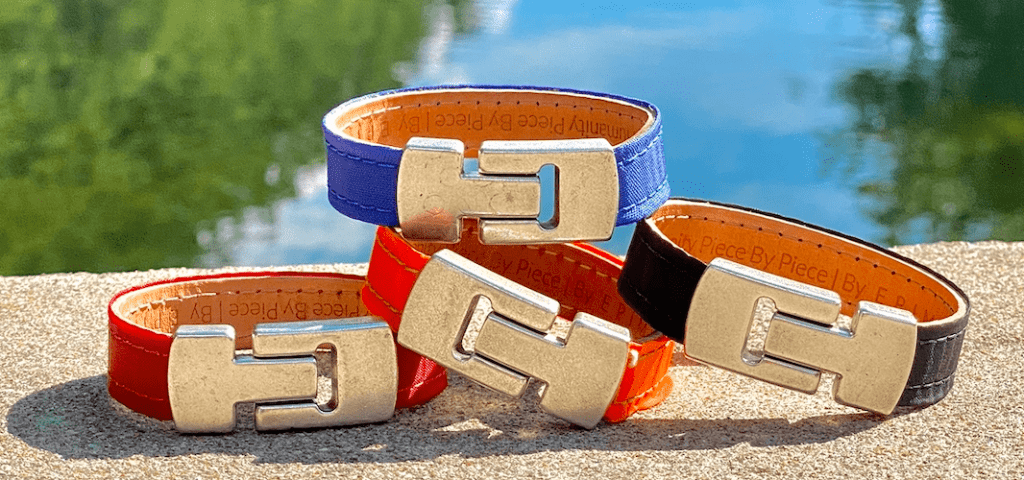 Four bracelets (red, orange, blue, and black) with silver clasp sitting on beige brick outside with water in the background. Good pandemic gifts for stationary travelers!