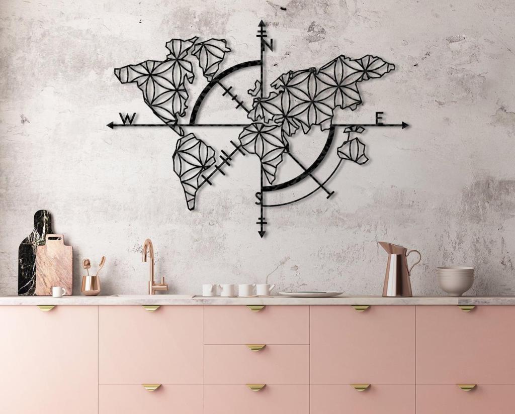 Metal world map wall art hanging above pink kitchenette