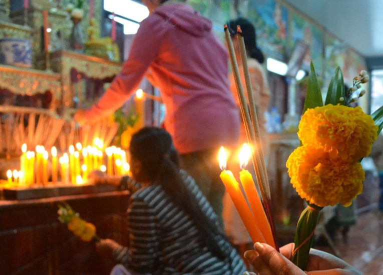 Traditional Almsgiving Ceremony at Temple with Candles, Incense and Flowers