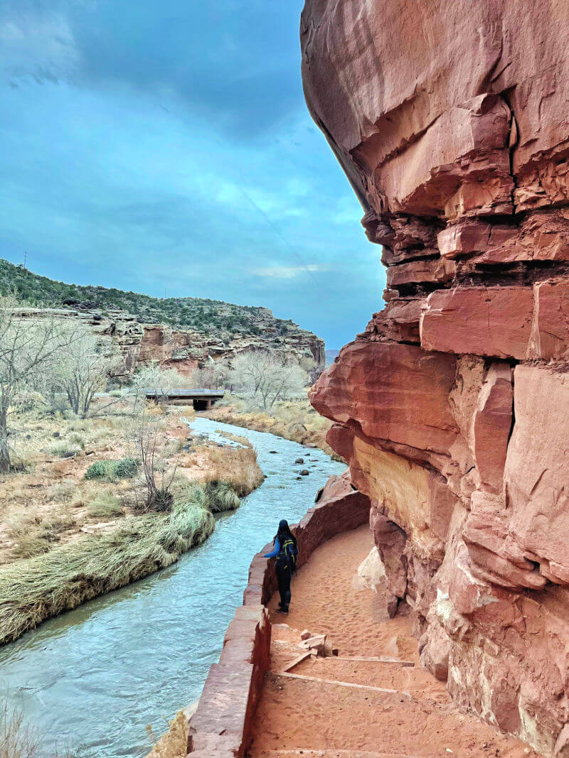 woman looking out at river next to towering red rocks