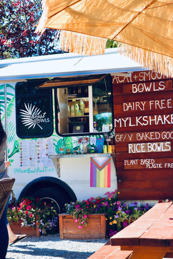 bohemian food truck with potted flowers surrounding it