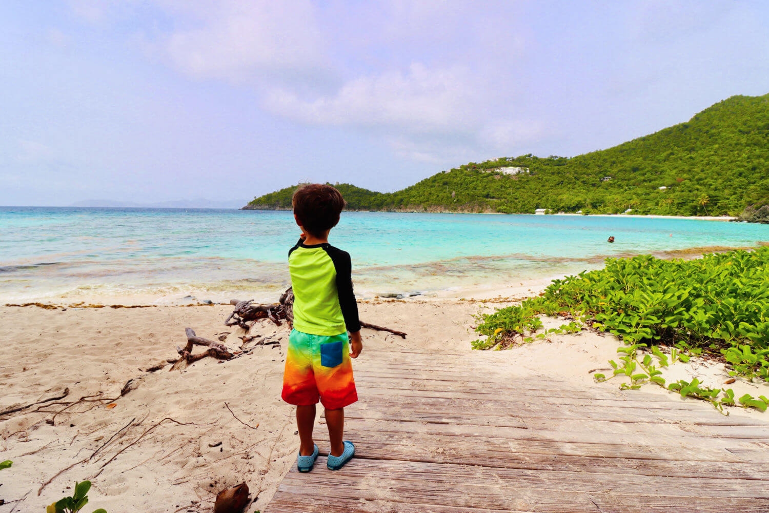 Young kid on St. John Island looking out at beautiful blue beach