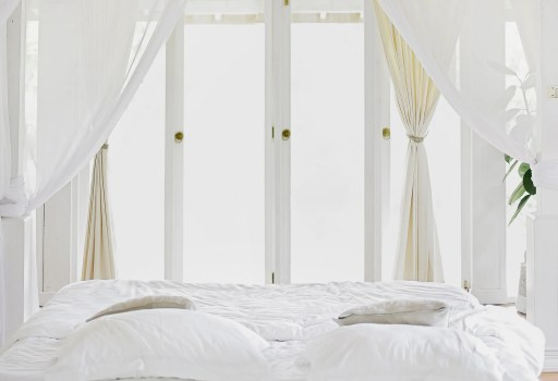 white bed infront of window with white drapes to create a perfect bedroom