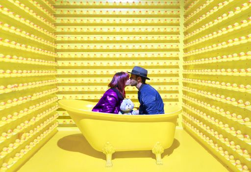 people sat in a yellow bathtub holding a blue carebear surrounded by yellow rubber ducks lining walls