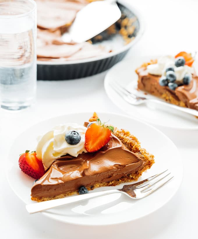 Vegan chocolate mousse pie with berries on a white plate