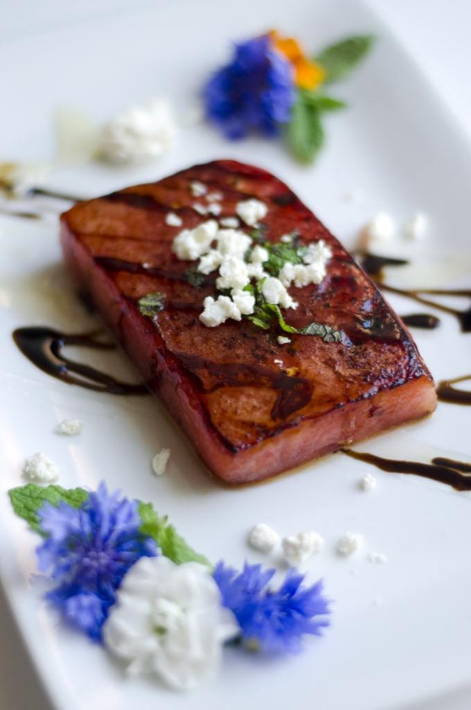 Pan-Seared Watermelon Steak with edible flowers, feta cheese, and balsamic vinegar reductions